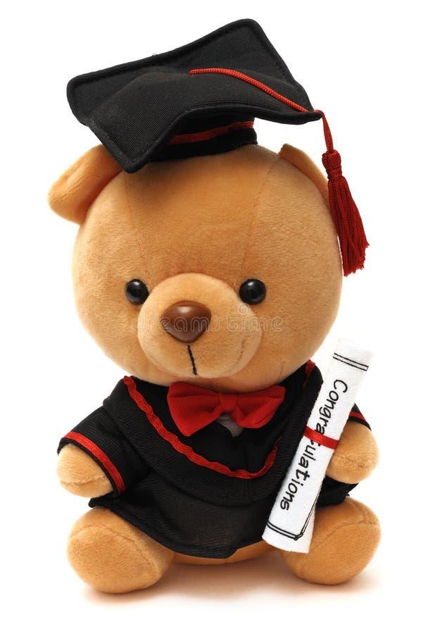 Um urso de peluche macio do brinquedo que veste um vestido da graduação fotografia de stock royalty free