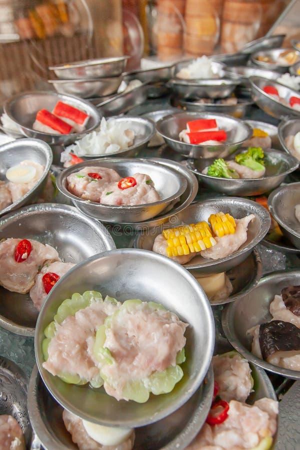 Um vário de bolinhas de massa da flâmula de Dim Sum serviu em placas de aço inoxidável pequenas em um restaurante chinês local em foto de stock