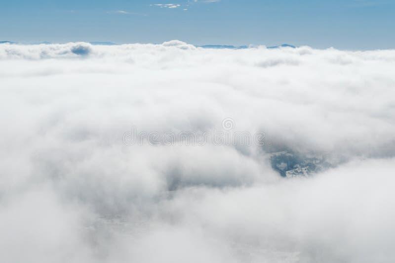 Um vale nevado coberto com as nuvens do ar imagens de stock royalty free