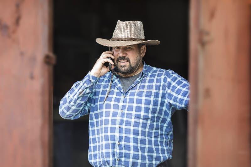 Um vaqueiro com um telefone celular em um chapéu e em uma barba fotografia de stock