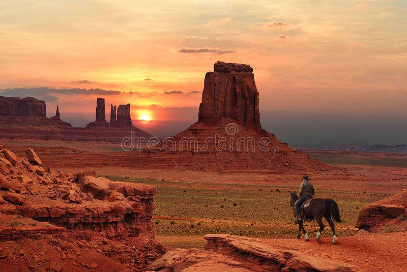 Um vaqueiro em um cavalo no por do sol no parque tribal do vale do monumento na beira do Utá-Arizona, EUA imagens de stock royalty free