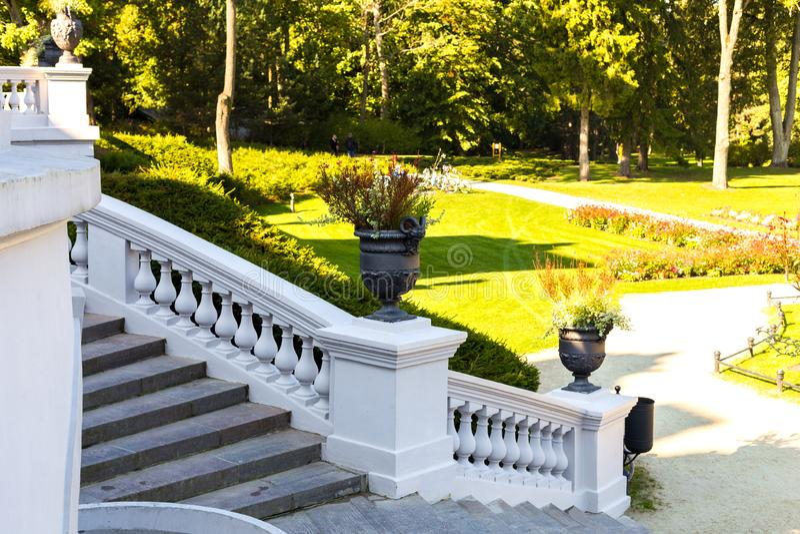 Um vaso com figuras antigas decora uma escadaria branca em um parque do outono imagem de stock