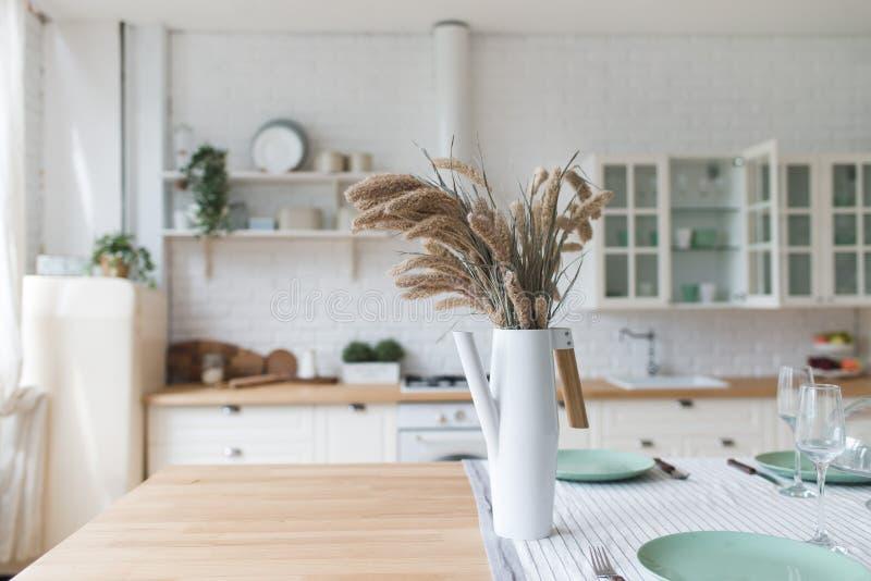 Um vaso com flores secas em uma tabela Cozinha cl?ssica escandinava com detalhes de madeira e brancos, design de interiores minim foto de stock