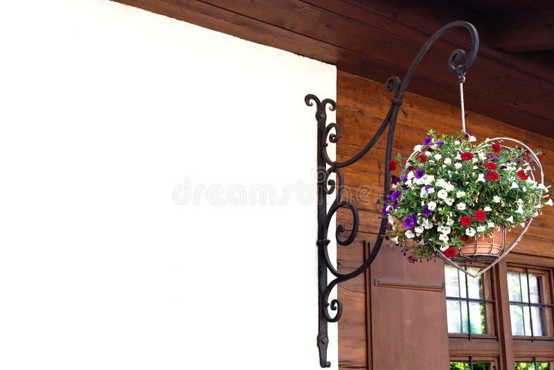 Um vaso de flores na forma de um coração pendura em um suporte forjado em uma casa de madeira imagem de stock