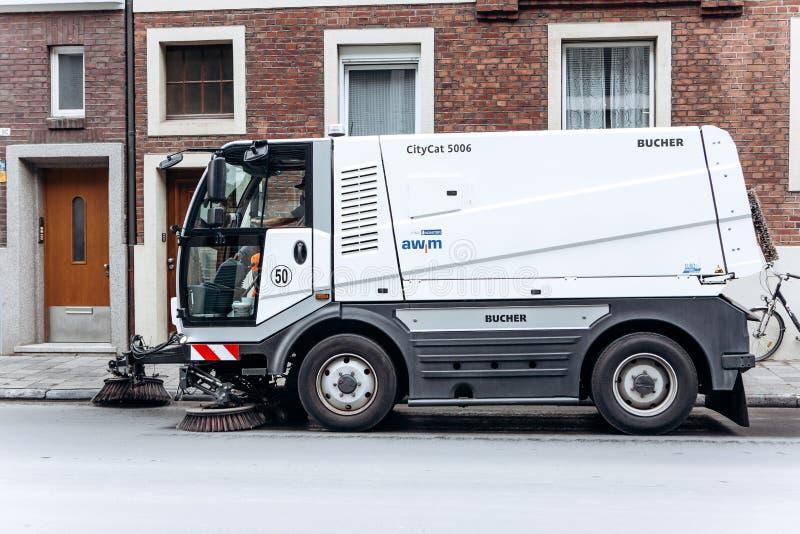 Um veículo especial da limpeza do caminhão ou da rua monta ao longo da estrada e limpa a rua da sujeira e da poeira fotografia de stock