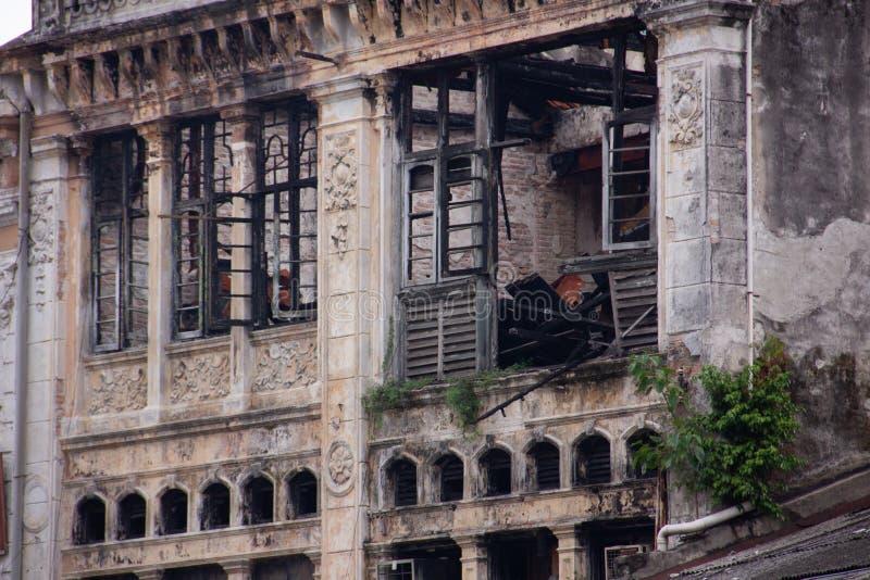 Um velho prédio histórico arruinado com vestígios de fogo, fuligem nas paredes perto das janelas foto de stock
