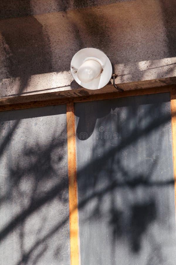 Um velho uma únicas ampola e lâmpada exteriores na porta da parede dianteira da casa, close up fotografia de stock royalty free