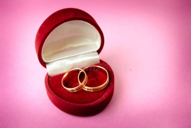 Um veludo festivo vermelho bonito da caixa de presente para duas o acoplamento, alianças de casamento com ouro precioso em volta  imagens de stock