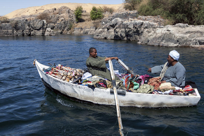 Um vendedor da lembrança e da matéria têxtil e seu filho remam seu barco para um barco de turista no Nilo do rio perto de Aswan e foto de stock