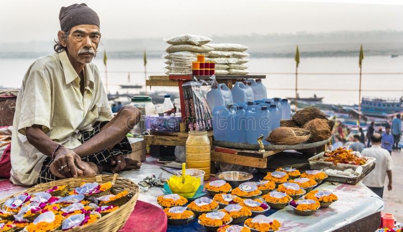 Um vendedor de flor senta-se em uma plataforma acima do Ganges River com os pés cruzados vendendo suas flores e velas em Varanasi imagem de stock