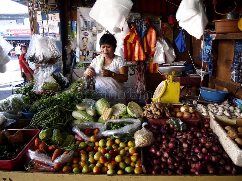 Um vendedor do mercado dentro de uma tenda das frutas e legumes em um mercado público imagem de stock royalty free
