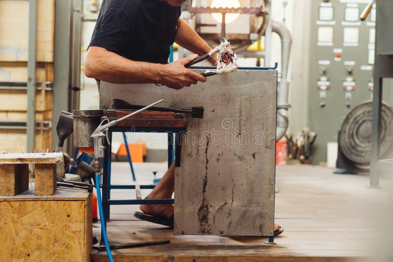Um ventilador de vidro que dá forma ao vidro derretido em uma obra de arte foto de stock royalty free