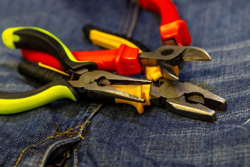 Um verde plástico brilhante de três cortadores de fio segura o amarelo vermelho em ferramentas do close-up do fundo das calças de imagens de stock