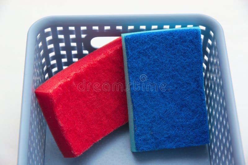 Um vermelho e uma esponja azul em uma cesta plástica imagens de stock