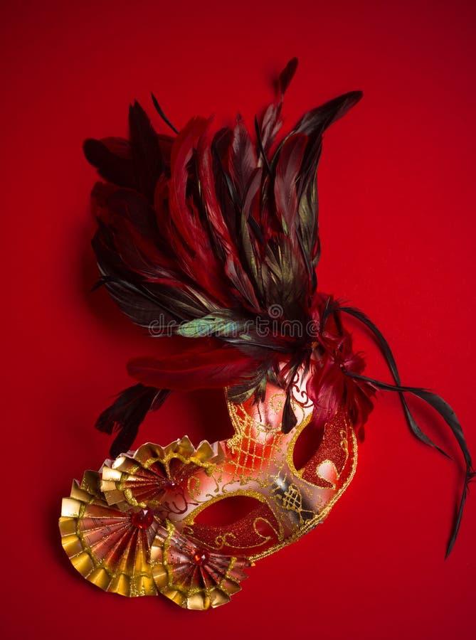 Um vermelho, um ouro e uma máscara preta do carnaval em um fundo vermelho imagens de stock