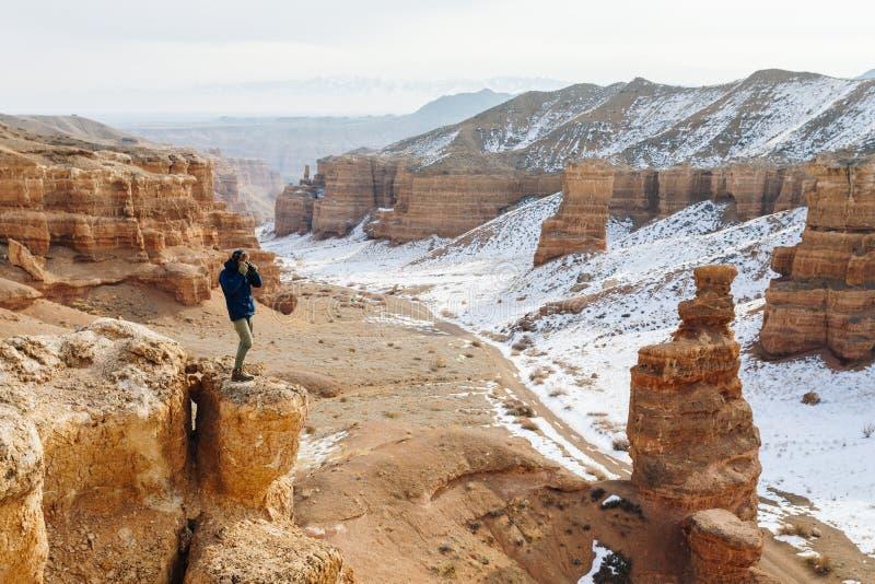 Um viajante alegre com uma câmera está na borda do penhasco na garganta de Charyn em Cazaquistão imagens de stock