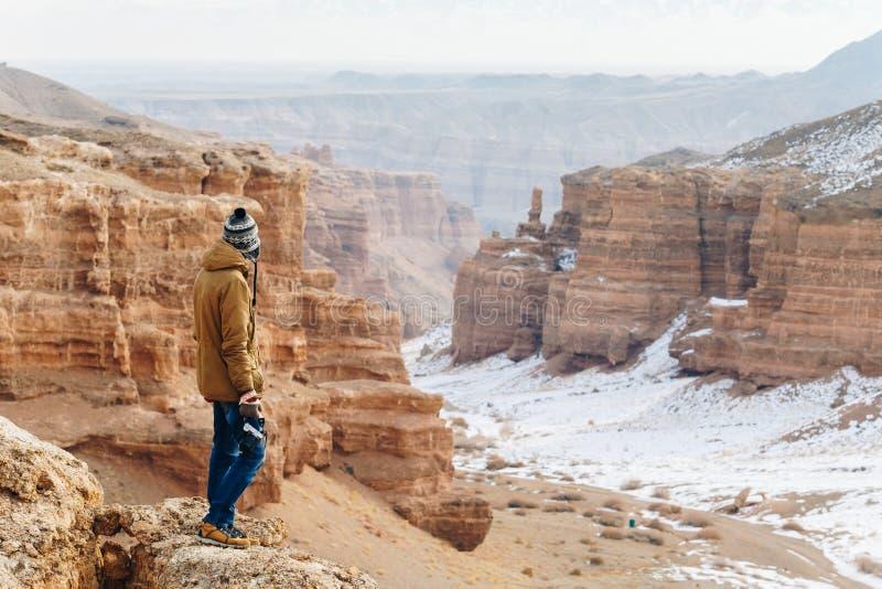 Um viajante alegre com uma câmera está na borda do penhasco na garganta de Charyn em Cazaquistão fotografia de stock royalty free
