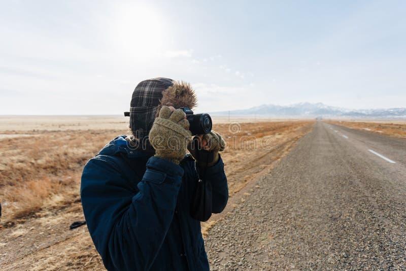 Um viajante alegre com uma câmera está na estrada no estepe do Cazaque completamente apenas fotos de stock royalty free