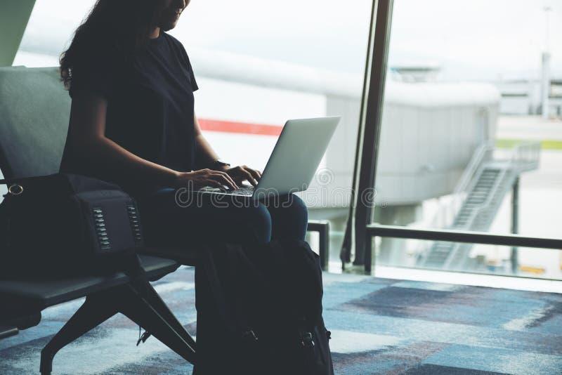 Um viajante da mulher que usa o laptop no aeroporto imagens de stock royalty free