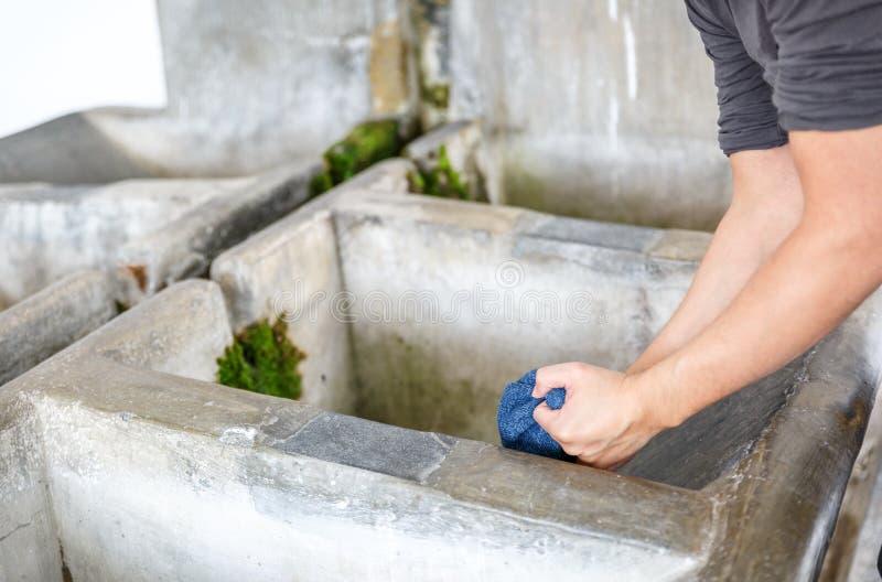 Um viajante lava seu tampão de lãs em uma lavanderia de pedra pública velha no La Alpujarra, Espanha fotografia de stock