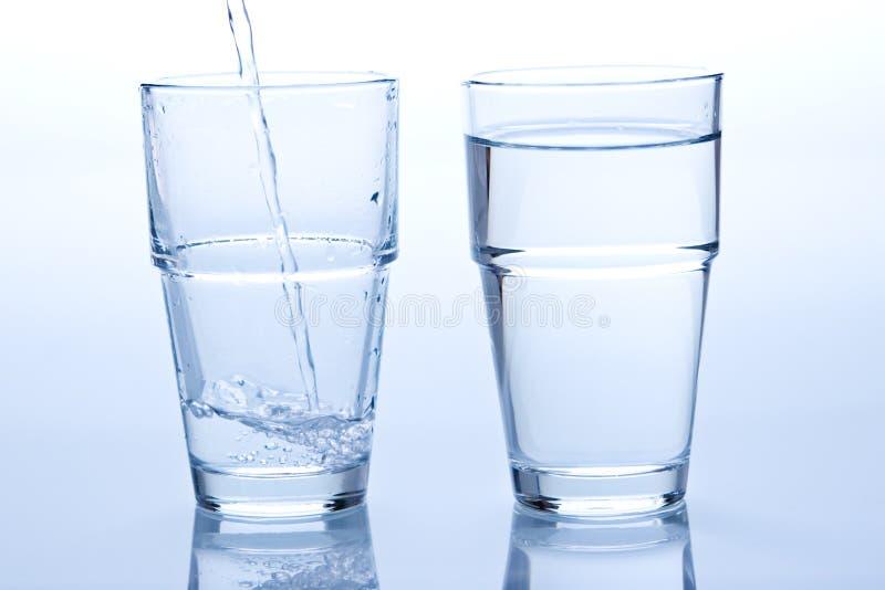 Um vidro cheio e vazio da água fotos de stock