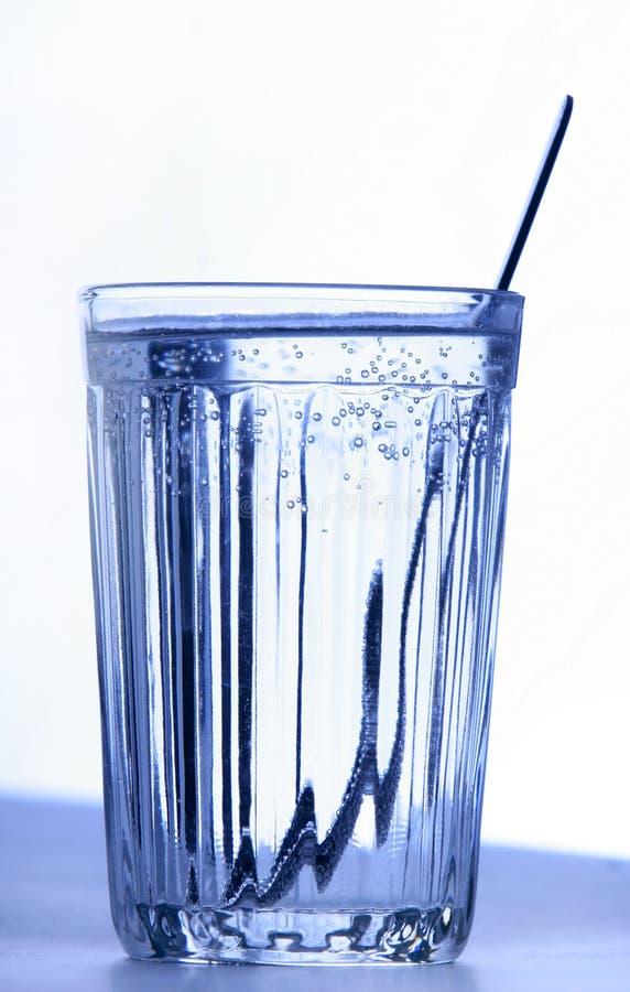 Um vidro com água e o teaspoon imagem de stock