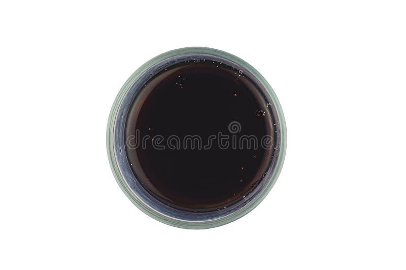 Um vidro completo da cor preta ventilada da cola com as bolhas isoladas no fundo branco Vista superior fotos de stock