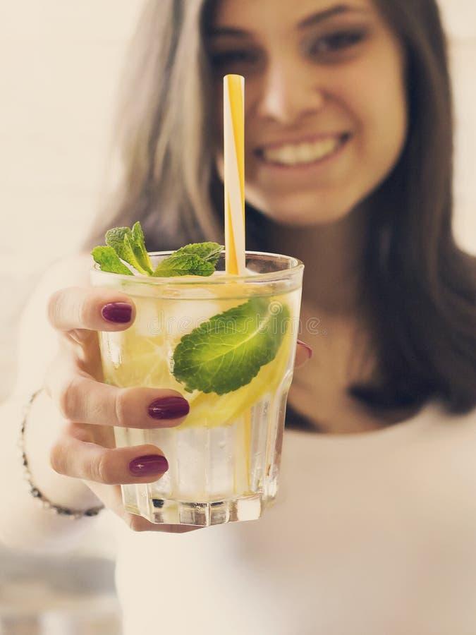 Um vidro da água da desintoxicação com limão, gelo e a hortelã fresca nas mãos de uma moça foto de stock royalty free