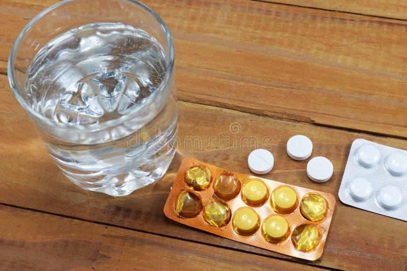 Um vidro da água e das tabuletas na tabela, uma descarga do ` s do doutor imagens de stock