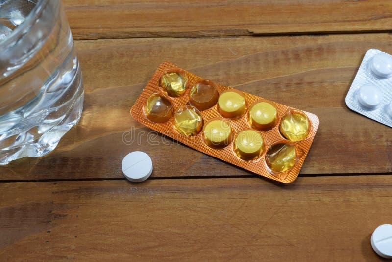 Um vidro da água e das tabuletas na tabela, uma descarga do ` s do doutor imagem de stock royalty free