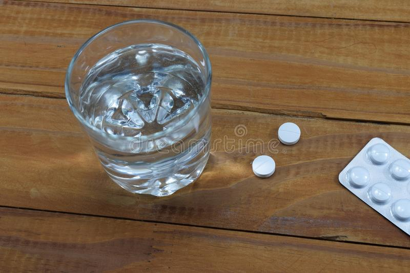 Um vidro da água e das tabuletas na tabela, uma descarga do ` s do doutor fotos de stock