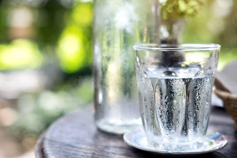 Um vidro da água fria e da garrafa na tabela de madeira fotos de stock royalty free