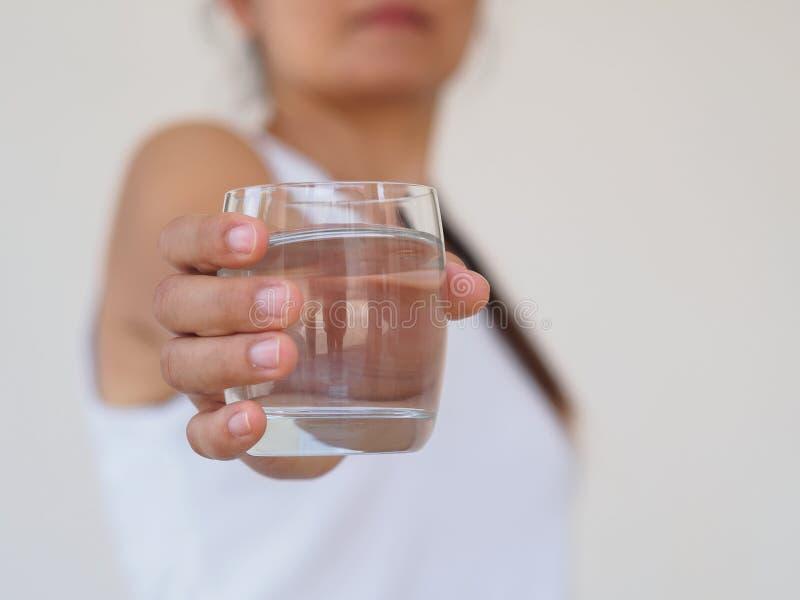 Um vidro da água mineral limpa nas mãos do ` s da mulher Conceito do envi imagem de stock