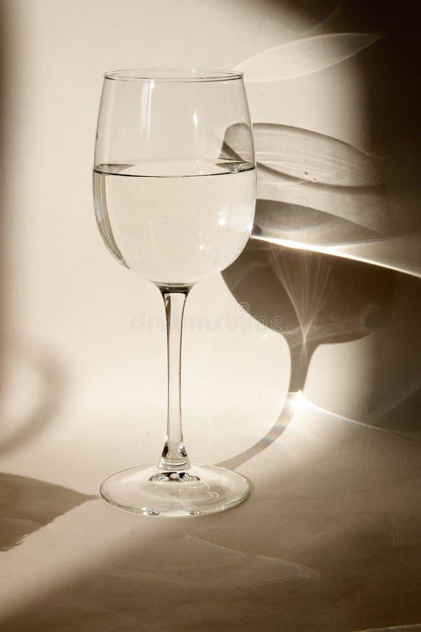Um vidro da agua potável em um fundo claro com sombras e reflexões imagem de stock royalty free