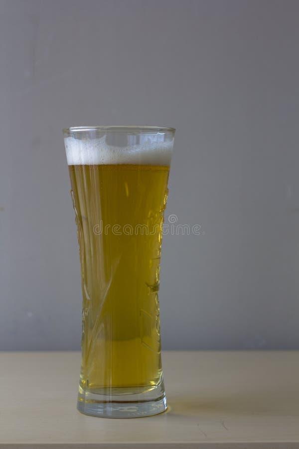Um vidro da cerveja clara no backgound cinzento vida im?vel minimalistic de uma caneca de cerveja escura fotos de stock royalty free
