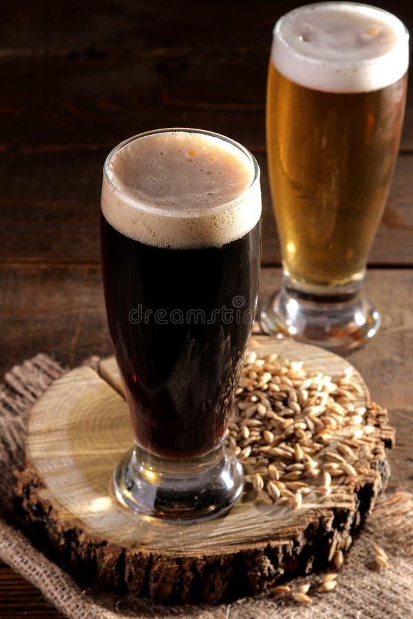 Um vidro da cerveja escura e clara em um suporte de madeira com grões da cevada em uma tabela marrom fotografia de stock