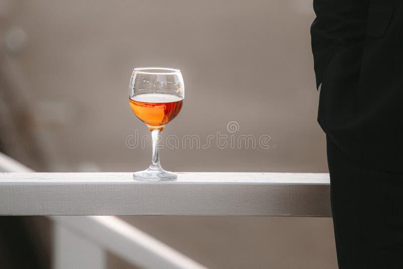 Um vidro de suportes da aguardente nos trilhos durante um casamento imagem de stock