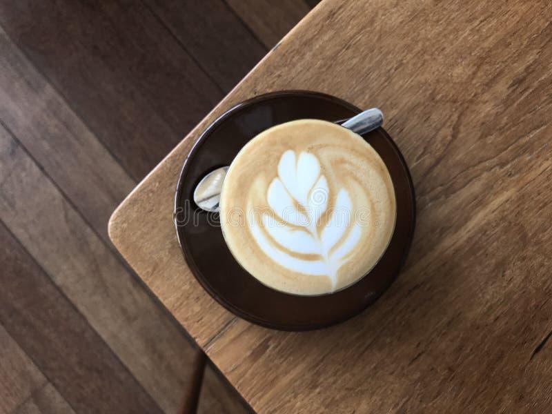 Um vidro do café quente da arte do latte na tabela de madeira de canto fotografia de stock royalty free