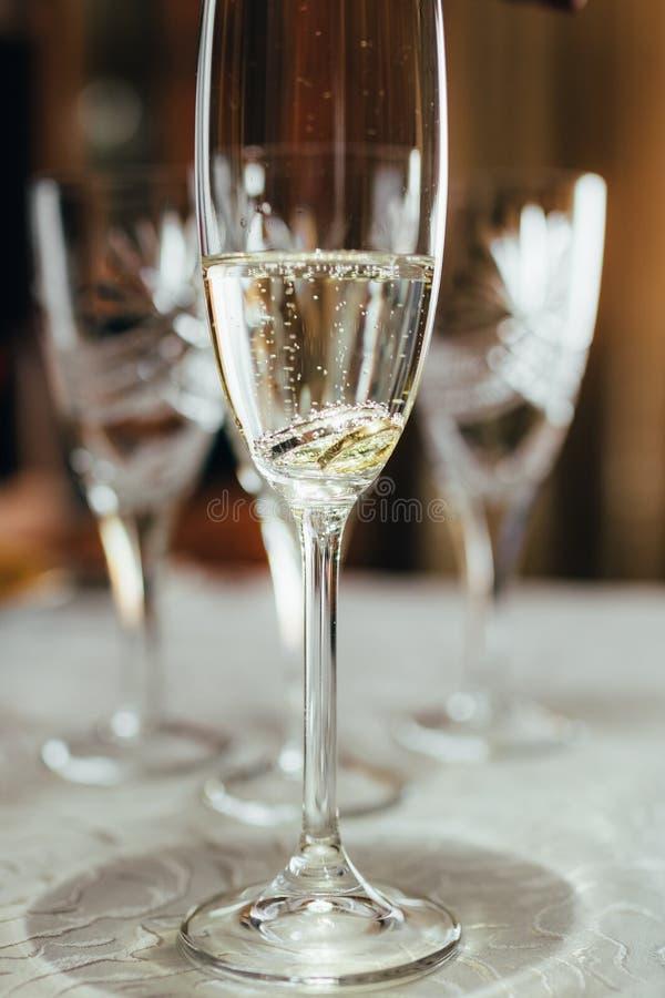 Um vidro do champanhe e das alian?as de casamento imagens de stock royalty free