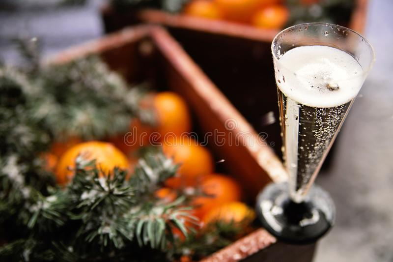 Um vidro do champanhe e de uma caixa das tangerinas imagem de stock