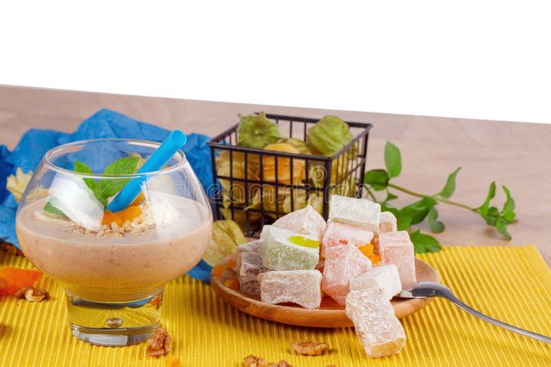 Um vidro do cocktail, da hortelã fresca, do abricó secado, das nozes, da placa do lokum do rahat ou do lokum, physalis, em um bra imagens de stock royalty free