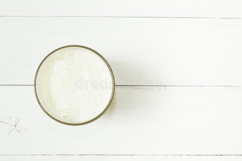 Um vidro do iogurte do leite em uma tabela de madeira branca foto de stock royalty free