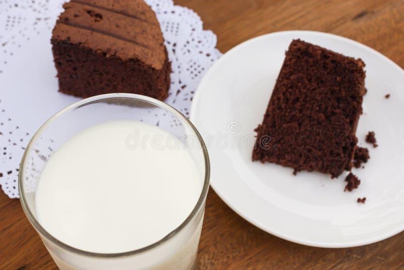 Um vidro do leite com fundo do bolo de chocolate fotografia de stock royalty free