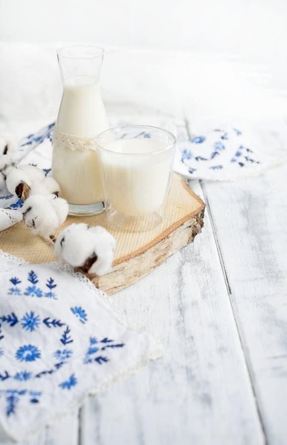 Um vidro do leite e de uma garrafa do leite Um ramo do algodão e uma toalha bordados com flores azuis Fundo branco e espaço livre fotografia de stock royalty free