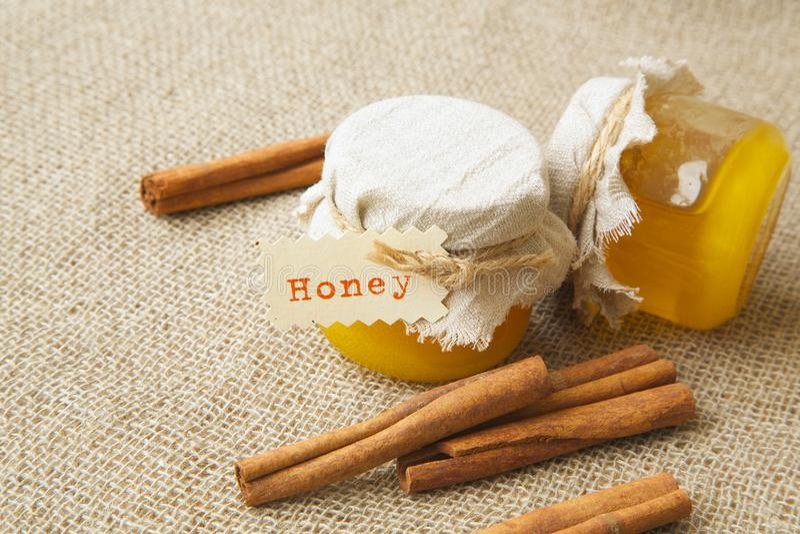 Um vidro do mel com canela imagem de stock