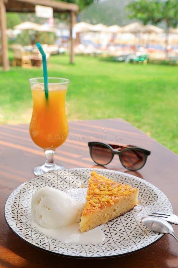 Um vidro do suco de laranja fresco e uma fatia de torta alaranjada com gelado de baunilha para o café da manhã durante as férias  imagem de stock royalty free