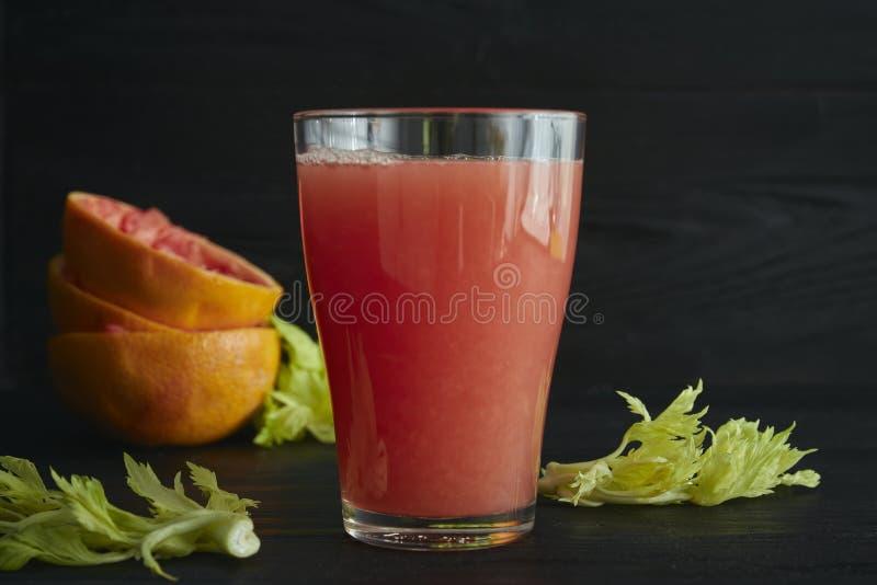 Um vidro do suco de toranja recentemente espremido com close-up das fatias da toranja em um fundo preto fotos de stock