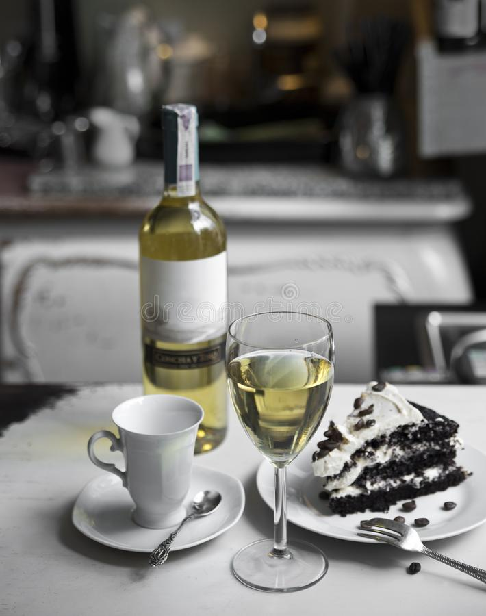 Um vidro do vinho branco, do copo, do bolo de chocolate e de uma garrafa do vinho em um fundo retro fotos de stock