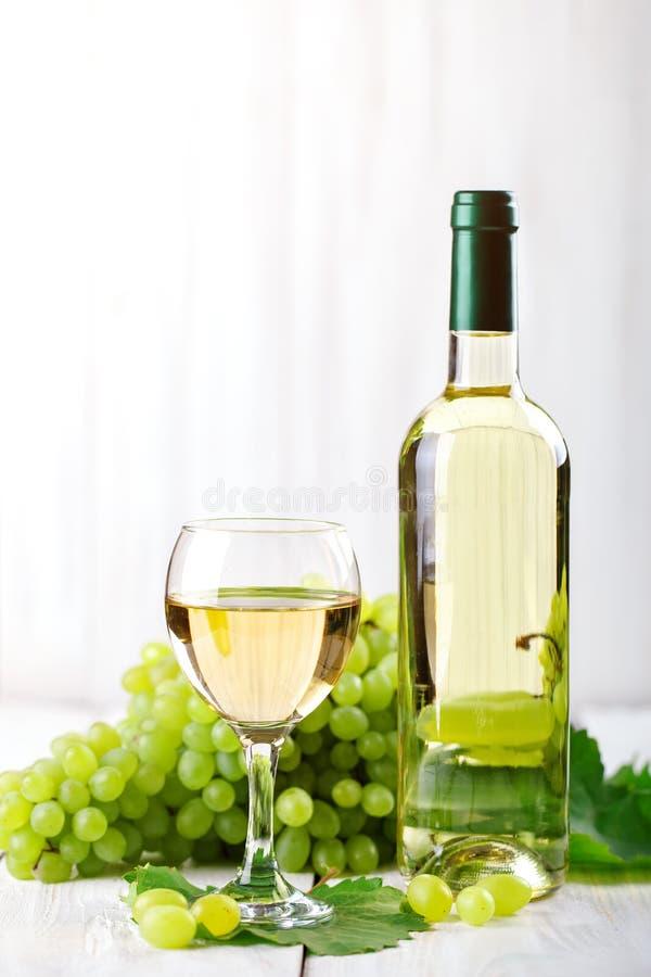 Um vidro do vinho branco, de uvas frescas e de uma garrafa do vinho branco em uma tabela de madeira foto de stock royalty free
