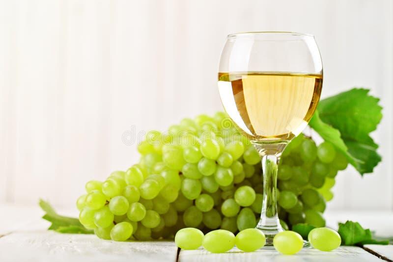 Um vidro do vinho branco e de uvas frescas em uma tabela de madeira imagens de stock